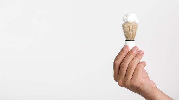 Übergeben sie das halten des rasierpinsels mit schaum über weißem hintergrund Premium Fotos