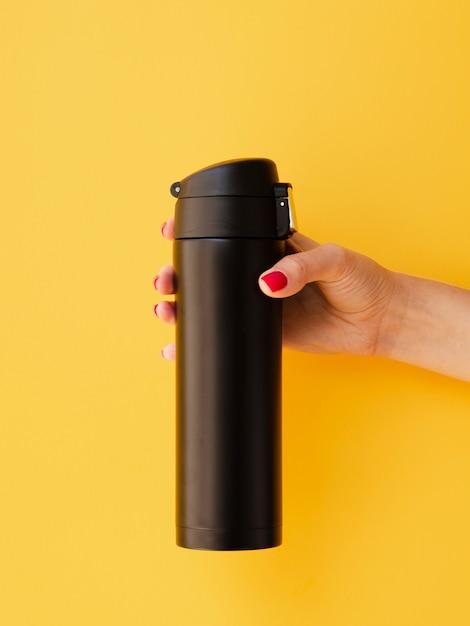 Übergeben sie das halten des thermosflaschenmodells auf gelbem hintergrund Kostenlose Fotos