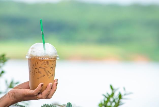 Übergeben sie das halten eines glases kalten espressokaffees baum und wasser der undeutlichen ansichten des hintergrundes. Premium Fotos