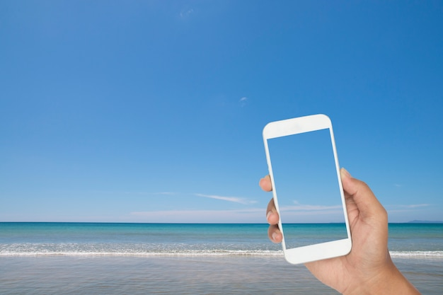 Übergeben sie das halten von smartphone mit tropischem meer und strand als hintergrund Premium Fotos