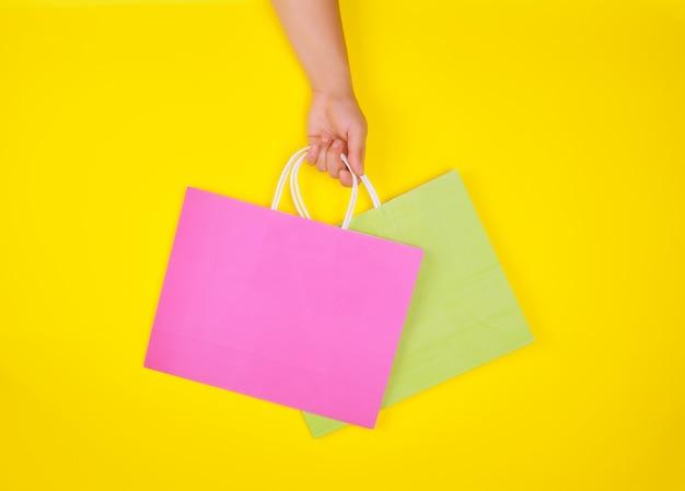 Übergeben sie das halten von zwei papiereinkaufstaschen auf einem gelben hintergrund Premium Fotos