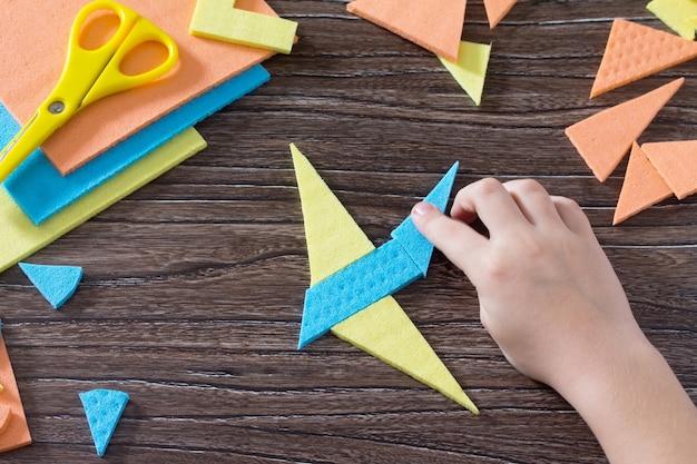 Übergeben sie das kind in der figur flugzeug tangram puzzle quadratischen holztisch oben gesammelt. Premium Fotos