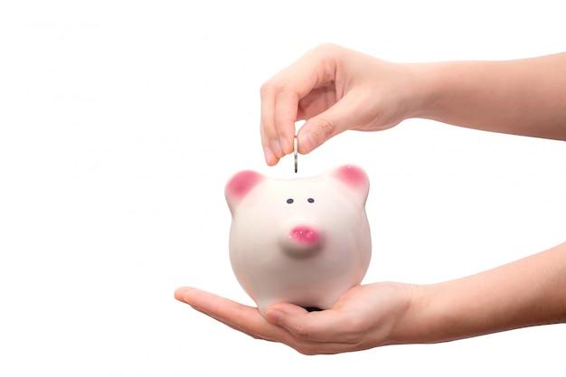 Übergeben sie das setzen der münze in das sparschwein, das auf weißem hintergrund lokalisiert wird. Premium Fotos