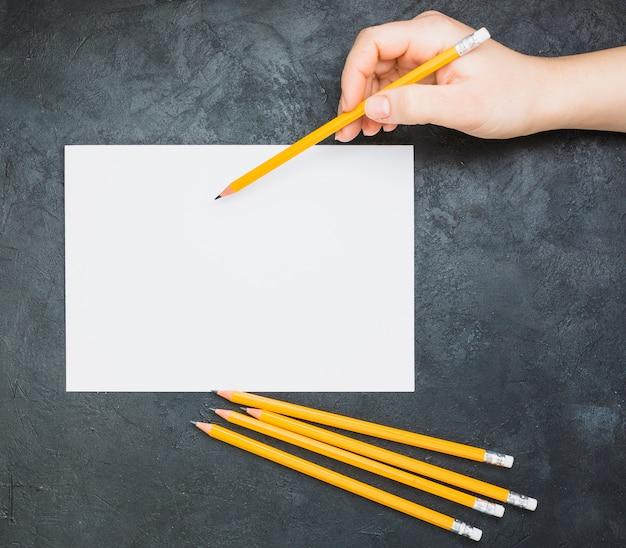 Übergeben sie das skizzieren auf leerem weißbuch mit einem bleistift auf schwarzem hintergrund Kostenlose Fotos