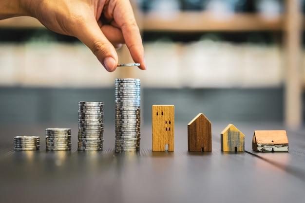 Übergeben sie das wählen der reihe des münzengeldes auf hölzerner tabelle und miniholzhaus, Premium Fotos