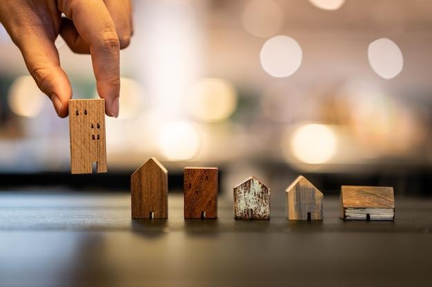 Übergeben sie das wählen des miniholzhausmodells vom modus auf hölzerner tabelle Premium Fotos