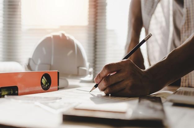Übergeben sie den berufsarchitekten, ingenieur oder innenhände, die mit plan zeichnen Premium Fotos