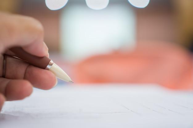 Übergeben sie den geschäftsmann, der silbernen stift hält, um kenntnisse über weiße schreibarbeit oder dokument am konferenzsitzungsraum zu nehmen Premium Fotos