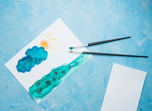 Übergeben sie gezogene zeichnung auf weißbuch mit malerpinsel über blauem hintergrund Kostenlose Fotos