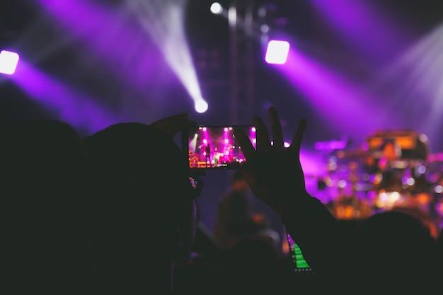 Übergeben sie griff ein intelligentes telefon, das foto macht oder video des konzertstadiums notiert Premium Fotos