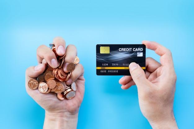Übergeben sie griffkreditkarte und münzen- oder bargeldhintergrund Premium Fotos