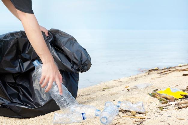 Übergeben sie mann mit der abfalltasche, die plastikflasche auf dem strand aufhebt Premium Fotos