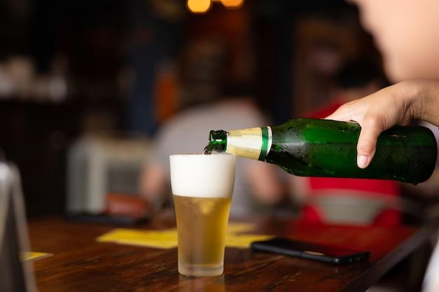 Übergeben sie strömendes bier von der flasche in ein glas im unschärfehintergrund. Premium Fotos