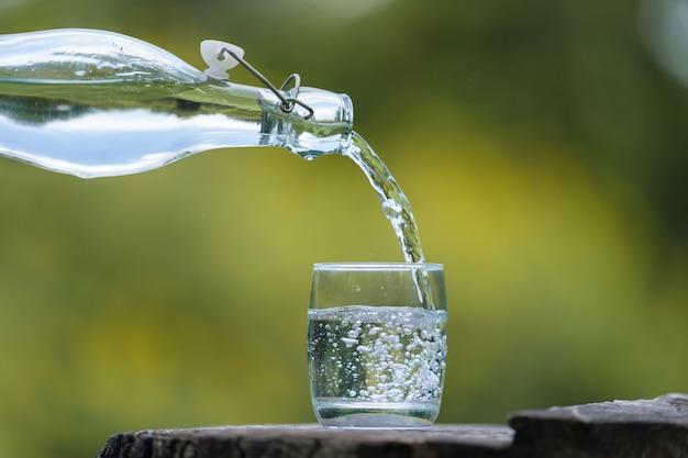 Übergeben sie strömendes getränkwasser von der flasche in glas mit natürlichem hintergrund Premium Fotos