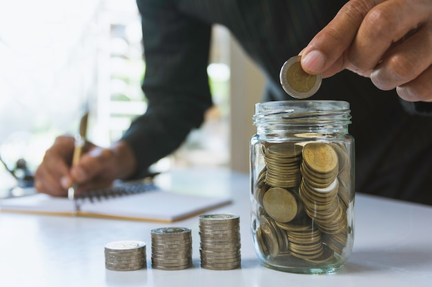 Übergeben sie tropfen eine münze mit dem geldmünzstapel, der für geschäft wächst. finanz- und rechnungswesenkonzept. Premium Fotos