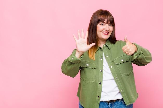 Übergewichtige frau lächelt und sieht freundlich aus, zeigt nummer sechs oder sechste mit der hand nach vorne und zählt herunter Premium Fotos