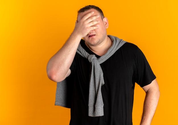Übergewichtiger mann in der brille, die das schwarze t-shirt trägt, das gesicht mit müder und gelangweilter hand bedeckt, die über orange wand steht Kostenlose Fotos