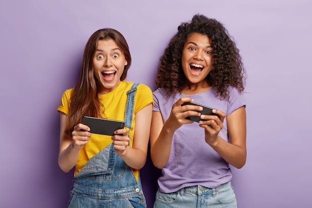 Überglückliche bloggerinnen gemischter rassen lachen und kommunizieren mit followern auf mobiltelefonen Kostenlose Fotos