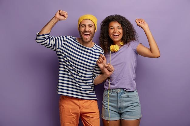 Überglückliche energetische tausendjährige multiethnische frau und mann haben spaß zusammen, hören musik, heben geballte fäuste, bewegen sich mit reim, lachen und posieren vor lila hintergrund Kostenlose Fotos