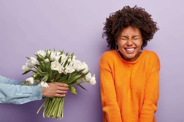 Überglückliche schöne junge lockige afroamerikanische dame erhält glückwunsch und blumen am geburtstag, unerkennbarer mann streckt hände und gibt frühlingsweiße tulpen, isoliert über lila wand. Kostenlose Fotos