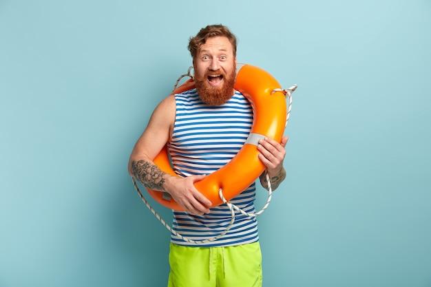 Überglücklicher männlicher rettungsschwimmer mit tätowierung, fuchsbart, posiert mit aufgeblasenem rettungsring, verhindert unfälle auf dem wasser, trägt sommerkleidung Kostenlose Fotos