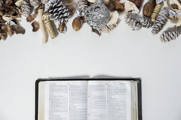 Überkopfaufnahme einer geöffneten bibel in der nähe von tannenzapfen und einer verzierung auf einer weißen oberfläche Kostenlose Fotos