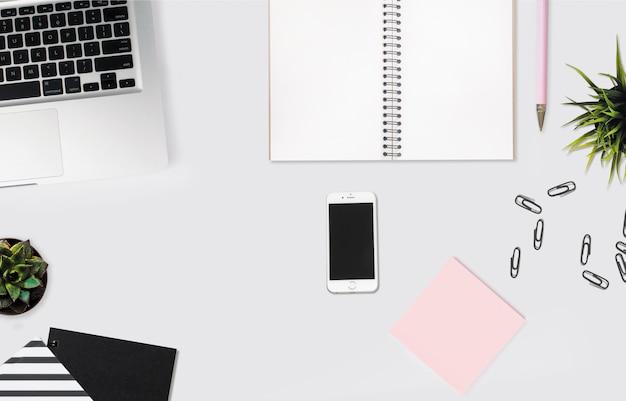 Überkopfaufnahme eines smartphones auf einem weißen schreibtisch mit einem notizbuch, rosa haftnotizen und büroklammern Kostenlose Fotos