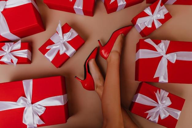 Überkopffoto der schlanken dame, die neben neujahrsgeschenken liegt. weibliche beine in roten schuhen. Kostenlose Fotos