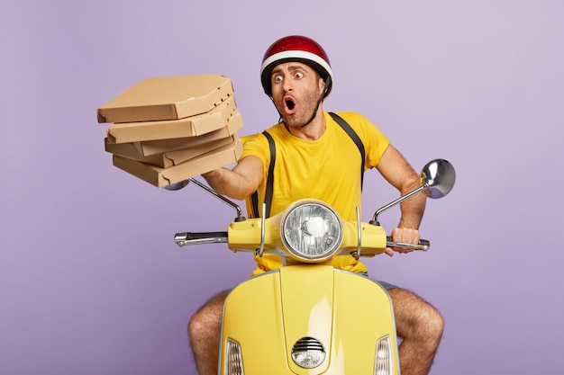 Überladen sie vielbeschäftigten lieferboten, der gelben roller fährt, während sie pizzaschachteln halten Kostenlose Fotos