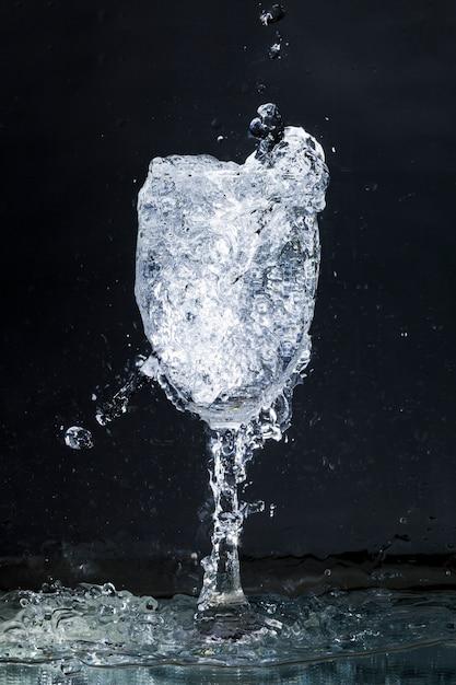 Überlaufendes wasserglas auf dunklem hintergrund Kostenlose Fotos