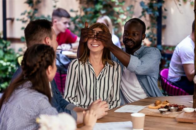 Überraschen sie von einem afrikanischen freund zu einem kaukasischen mädchen auf der freiluftterrasse eines restaurants Kostenlose Fotos
