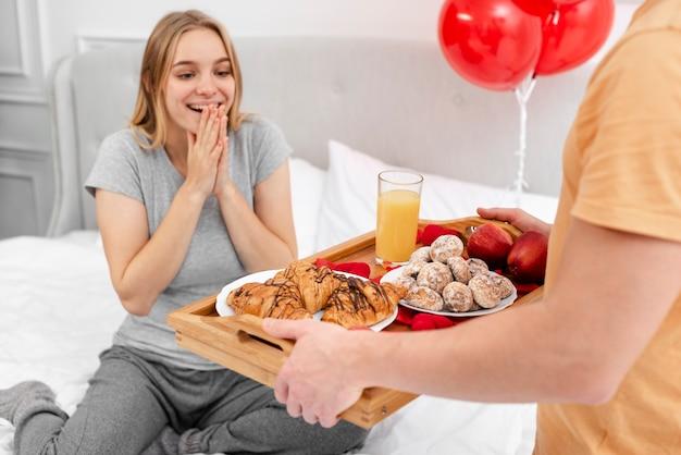 Überraschende frau des nahaufnahmemannes mit frühstück Kostenlose Fotos