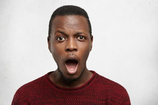 Überrascht emotionaler junger schwarzer mann, der faszinierten blick verblüfft, mund weit öffnet und augenbrauen hochzieht, schockiert von hohen verkaufspreisen, isoliert stehend Kostenlose Fotos