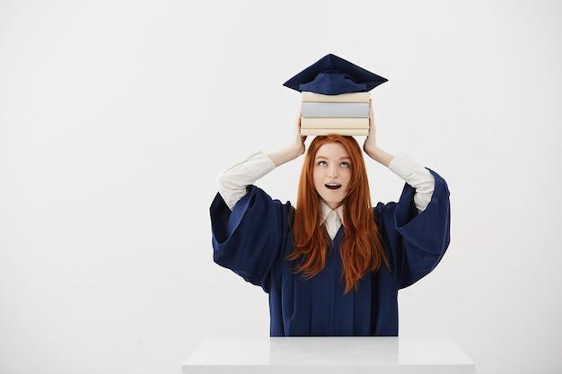 Überraschte absolventin der frau, die bücher auf kopf unter kappe hält. Kostenlose Fotos