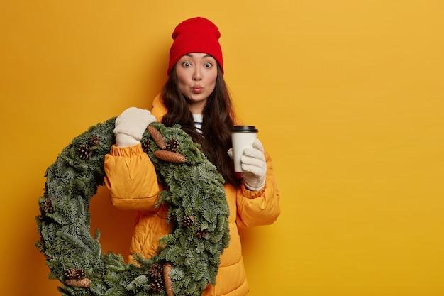 Überraschte ethnische frau trinkt aromatischen kaffee, trägt handgemachten weihnachtskranz, in winterkleidung gekleidet, weiße handschuhe hält die lippen rund Kostenlose Fotos