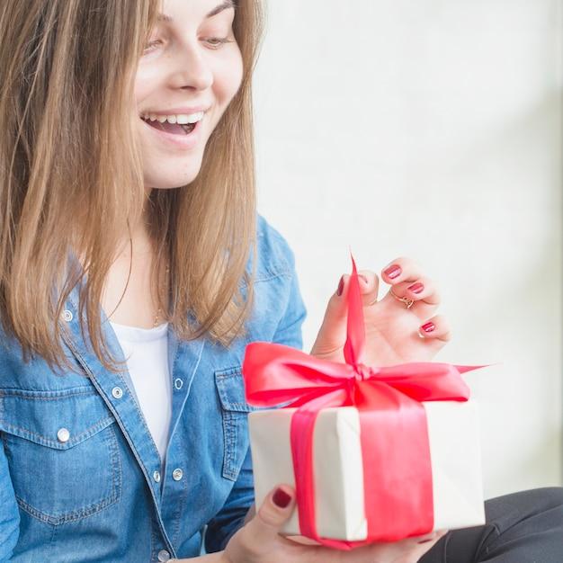 Überraschte frau, die geburtstagsgeschenkbox auspackt Kostenlose Fotos