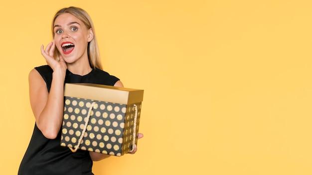 Überraschte frau, die geschenkboxkopierraum hält Kostenlose Fotos
