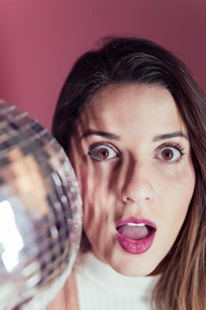 Überraschte frau, die mit discokugel steht Kostenlose Fotos