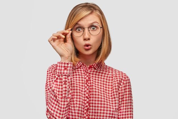 Überraschte frau mit europäischem aussehen, die von plötzlichen nachrichten in der welt verblüfft ist, starrt durch eine brille Kostenlose Fotos