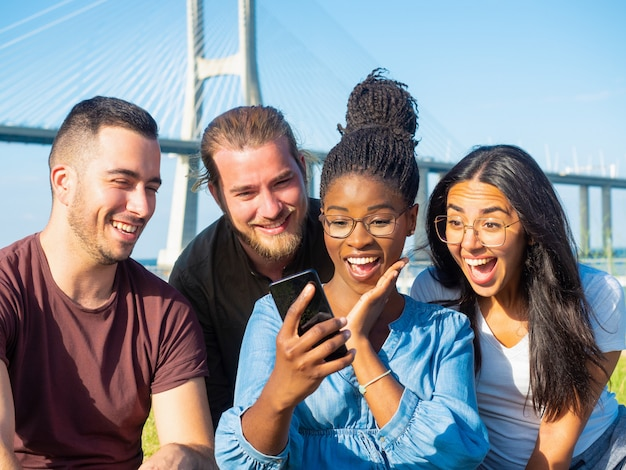 Überraschte freunde, die den smartphone im freien verwenden Kostenlose Fotos