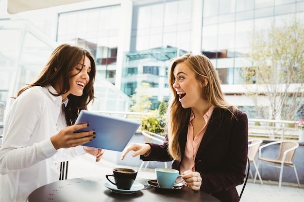 Überraschte freunde, die tablette im café betrachten Premium Fotos