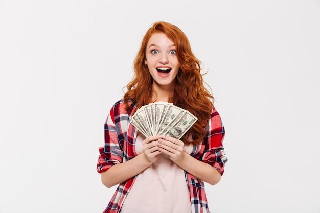 Überraschte hübsche junge rothaarige dame, die geld hält. Kostenlose Fotos