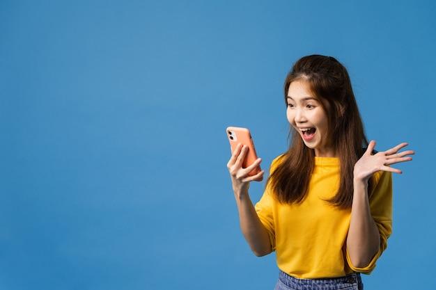 Überraschte junge asiatische dame, die handy mit positivem ausdruck verwendet, lächelt breit, gekleidet in freizeitkleidung und steht isoliert auf blauem hintergrund. glückliche entzückende frohe frau freut sich über erfolg. Kostenlose Fotos