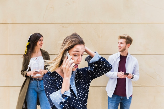 Überraschte junge frau, die am handy steht vor den freunden einander betrachtet spricht Kostenlose Fotos
