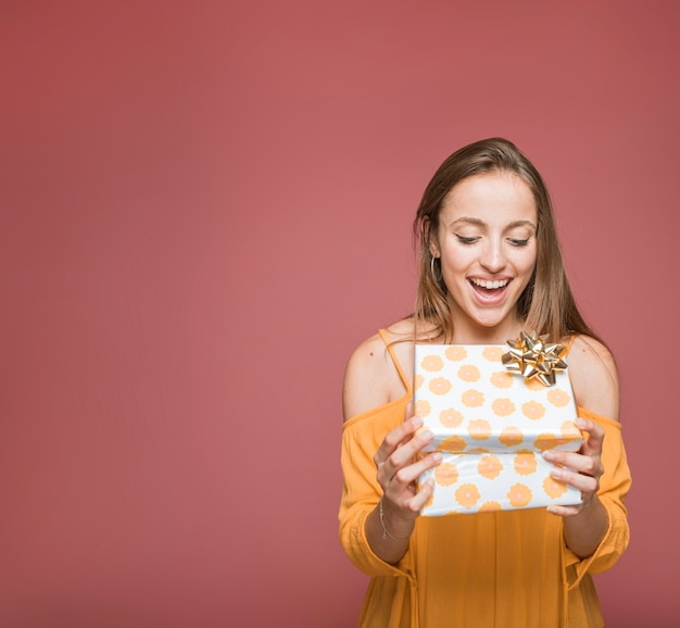 Überraschte junge frau, die blumengeschenkbox auf farbigem hintergrund betrachtet Kostenlose Fotos