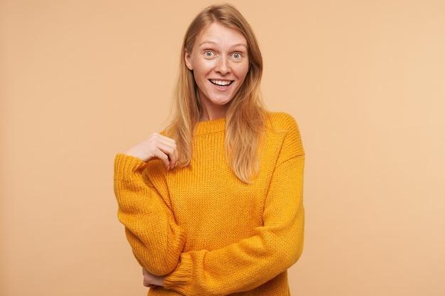 Überraschte junge rothaarige frau mit lässiger frisur, die ihr haar berührt und emotional schaut und auf beige im senfpullover posiert Kostenlose Fotos