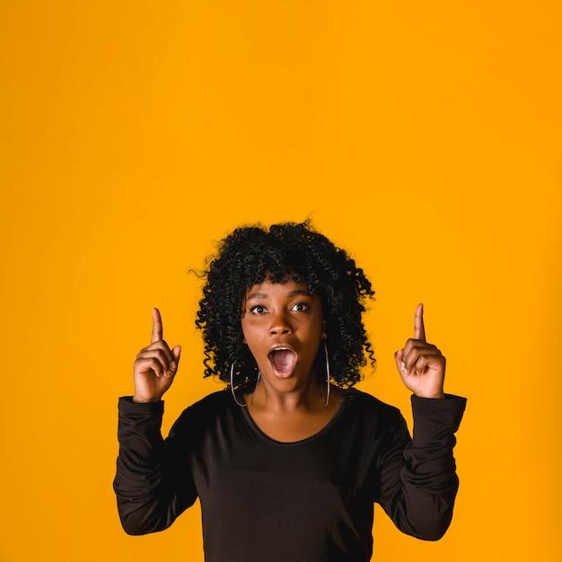 Überraschte junge schwarze frau, die oben im studio zeigt Kostenlose Fotos