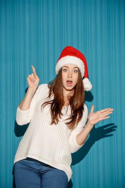 Überraschte weihnachtsfrau, die eine weihnachtsmütze trägt Kostenlose Fotos