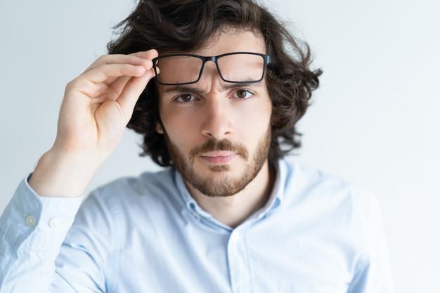 Überraschter attraktiver junger mann, der entlang der kamera anstarrt Kostenlose Fotos