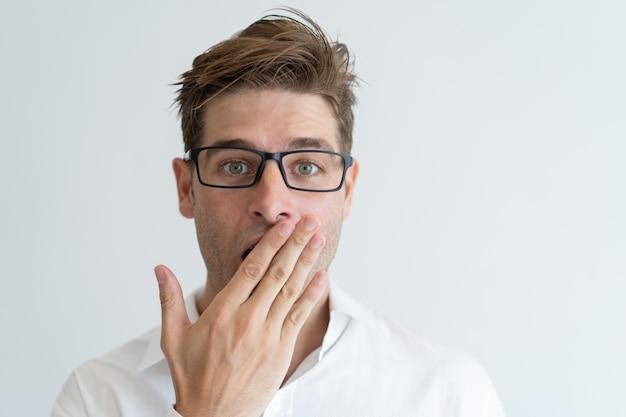 Überraschter bedeckungsmund des gutaussehenden mannes mit der hand Kostenlose Fotos